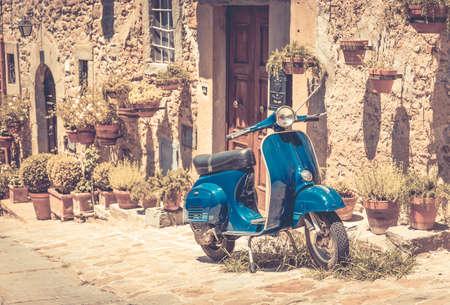 コルトーナ市街、トスカーナの古い建物の前にスクーター 写真素材