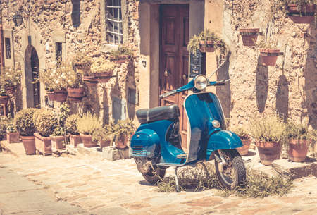 Scooter in de voorkant van het oude gebouw in de stad Cortona, Toscane