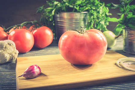 rustic food: Fresh tomato and vegetables arranged on a wooden table