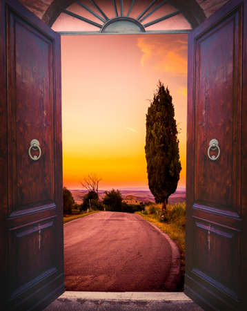 view of a wooden doorway: Old open door and cypress tree down the country road Stock Photo