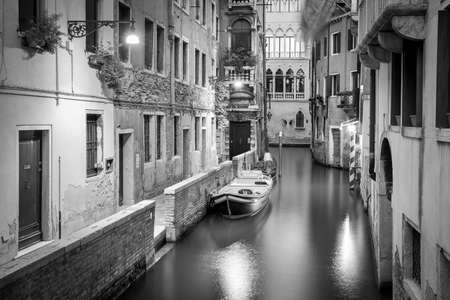 bw: BW scene from Venice. Narrow canal and boats in the evening. Stock Photo