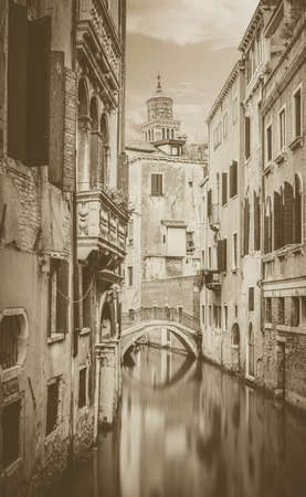 Vintage narrow canal with silky water in Venice, Italy