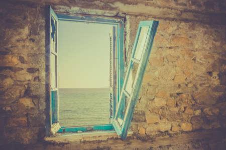 Old broken window with view of Aegean Sea