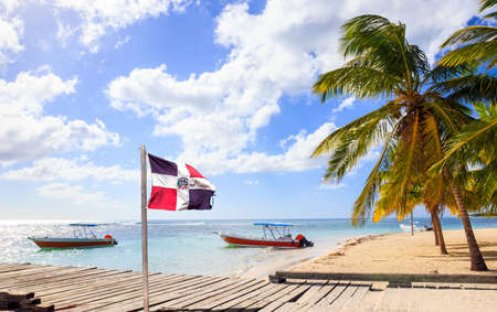 Caribbean beach and Dominican Republic flag on Saona island 스톡 콘텐츠