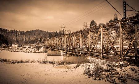 frozen river: Steel railway flyover over frozen river in winter Stock Photo