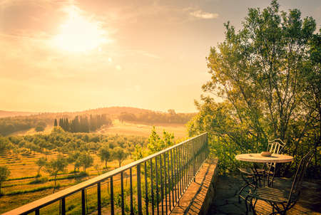 Sunlight over olive field in Tuscany with a table on a terrace in the foreground