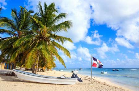 dominican republic: Beautiful caribbean beach and Dominican Republic flag