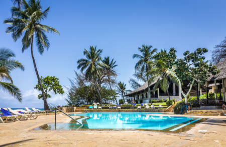 DIANI BEACH, KENYA - OCTOBER 09, 2018: Beautiful scenery of african luxury resort with empty swimming pool in the foreground, Kenya