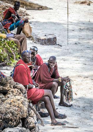 DIANI BEACH, KENYA - OCTOBER 14, 2018: Unindentified African men wearing traditional Masai clothes on Diani beach, Kenya