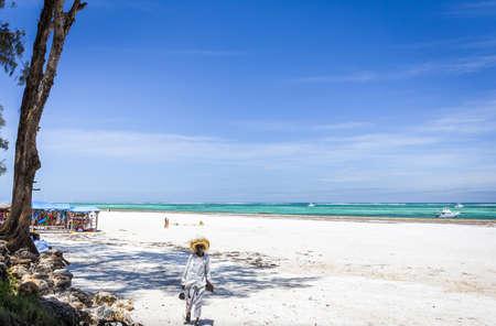 DIANI BEACH, KENYA - OCTOBER 14, 2018: Native african man and Diani beach seascape, Kenya