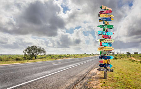 Funny different world directions signpost with distance to many different countries Stock Photo