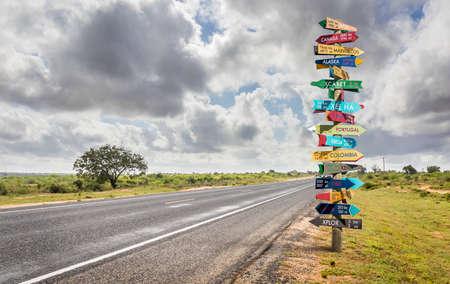 Panneau de direction du monde différent drôle avec distance à de nombreux pays différents