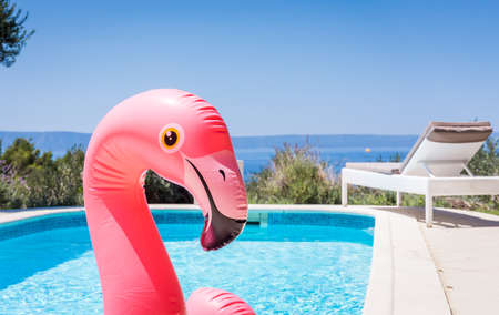 Pink flamingo waterbed in swimming pool with mediterranean sea in the background