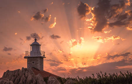 Amazing sunset with sunbeams and lighthouse in Makarska, Croatia