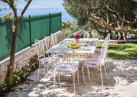 Beautiful garden, table setting prepared for a meal and view on Mediterranean sea