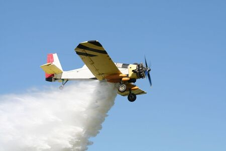 Airplane dropping water on a fire photo
