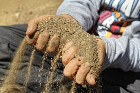 grasp: Sand Running Through Hands Of A Child  Stock Photo
