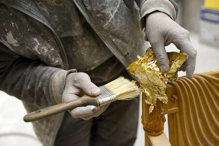 Carpenter Applying Golden Leaf To A Furniture
