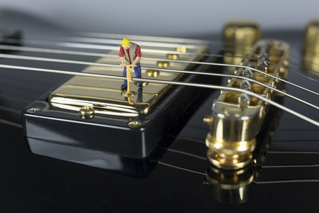 humbucker: Miniature Worker On Top Of Electric Guitar Pickup