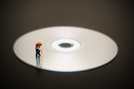 compact disc: Miniature Worker On Top Of Compact Disc