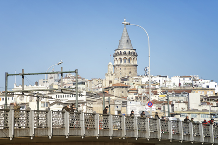 People fishing on top of Galata Bridge, Galata Tower can be seen at the background, Istanbul, Turkey