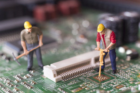 Miniature Workers On Top Of Circuit Board Stock Photo