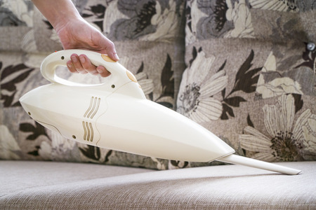 Hand Using Mini Vacuum Cleaner On A Couch