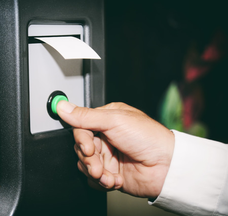 Hand pressing button and getting ticket from a machine