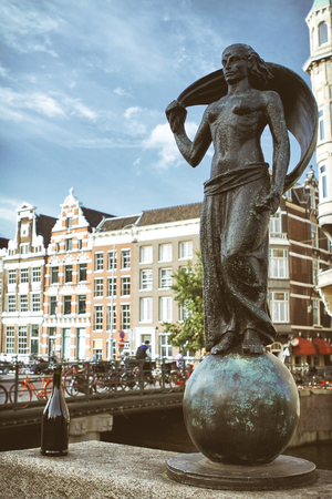 AMSTERDAM, NETHERLANDS, JULY 12, 2012: Statue Of Lady Fortune (Statue Vrouwe Fortuna) in front of traditional Dutch houses, statue is made by the sculptor Hildo Krop.