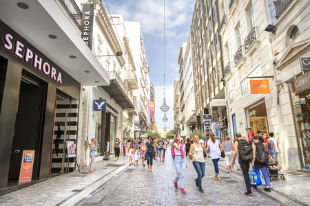 People walking and shopping at Ermou Street, one and a half kilometer-long road in central Athens, Greece,