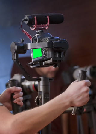 Hands Holding Camera Gimbal Stabilizer Loaded With Dslr Camera