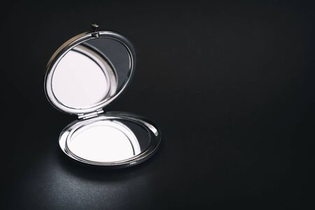 Foldable Pocket Mirror On A Dark Surface Stock Photo