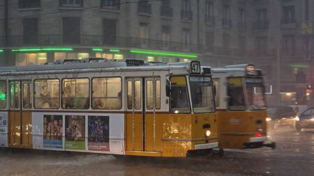 Yellow cable cars operating under heavy rain at Budapest, capital city of Hungary. Banco de Imagens