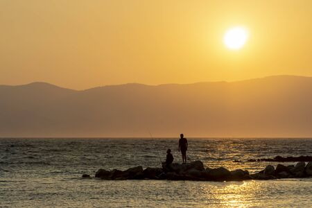 Silhouettes Of Men Fishing On Rocks At Sunset