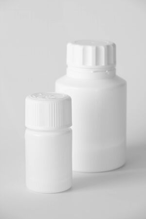 White Plastic Pill Bottles On A Gray Surface