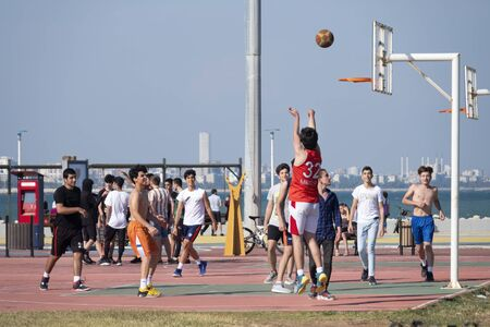 Young people playing basketball at a park at the coastline of Mersin, a large city and a port on the Mediterranean coast of southern Turkey.