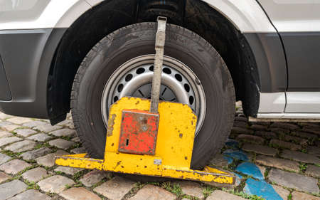 Wheel Clamp on a Poorly Parked Car without Authorization, Blue Zone for Residents Only, Bad Time and Place