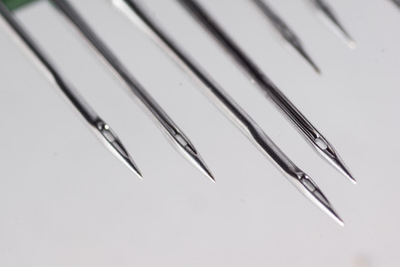 Industrial machine sewing needle. High resolution image depicting textile and fashion industry.