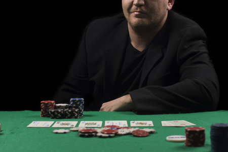 Poker table setup. High resolution image for gambling industry containning pokers chips, cards, green surface and person. Stock Photo