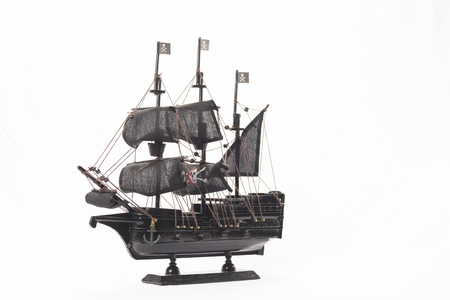 Black pirate boat model on white background. High resolution image.
