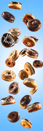 Multiple doughnuts on blue background. High resolution image for food industry. Reklamní fotografie