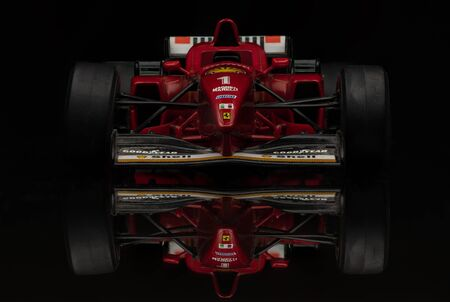 Vintage red Ferrari Formula 1 car on black background. High resolution image for racing industry.