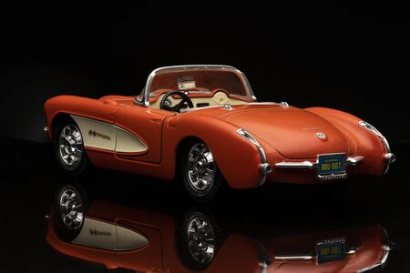 Orange Chevrolet Corvette 1957 on black background. High resolution image for automotive industry.