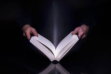 Person reading book with glowing light coming from inside of it. High resolutin image. 版權商用圖片