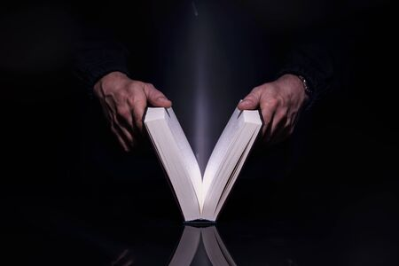 Person reading book with glowing light coming from inside of it. High resolutin image.