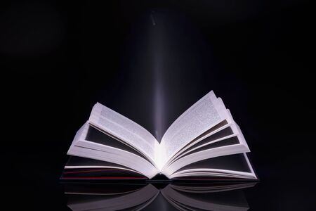 Book with glowing light coming from inside of it. High resolution image.