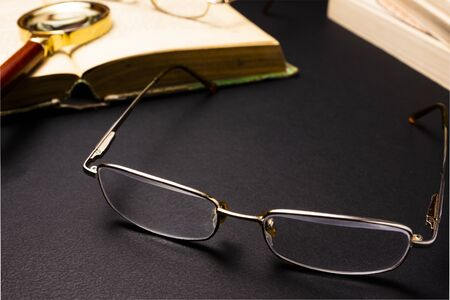 Books with glasses on black table and wooden background. High resolution image depicting reading/bokks industry.