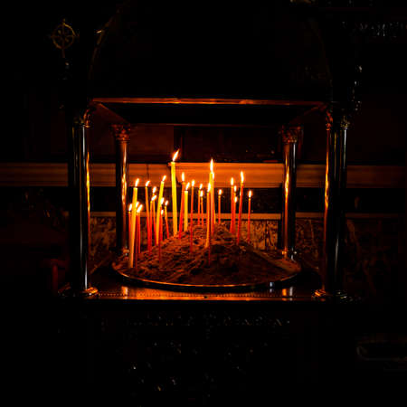 Candlestick with a few candles in dark and myserious atmosphere, square and symmetrical crop