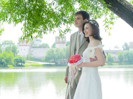 nuptial: Wedding couple near the water and monastery