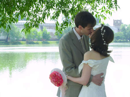 with fondness: Kissing couple near water and monastery Stock Photo